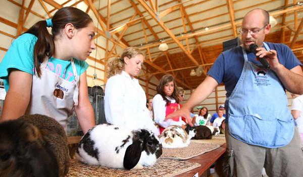 7-10-12<br /> Howard County Fair<br /> Sarrah Cummins, Kelsey Quinn and Allie Dicken listen to Todd Naragon judge their rabbits.<br /> KT photo | Tim Bath