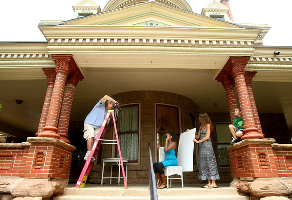 7-19-12<br /> Randy Rhudd takes photos of twelve year-old Keziah Pearson on the porch of the Seiberling Mansion. Tishelle Harris holds a white card while son Cameron Harris, 7, plays around.<br /> KT photo | Tim Bath