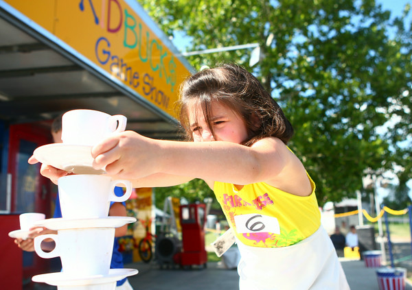 7-9-14<br /> Fair--Wednesday<br /> 7-year-old Sofie Hibschman stacks plates and cups on top of each other during one of the games in the Kid Buck$ Game Show at the Howard County 4H Fair Wednesday.<br /> Kelly Lafferty   Kokomo Tribune
