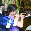 7-4-14<br /> Haynes Apperson Friday<br /> Scott Martin helps his granddaughter Daisy Button with the cork gun during a game at the Haynes Apperson Festival on Friday afternoon.<br /> Kelly Lafferty   Kokomo Tribune
