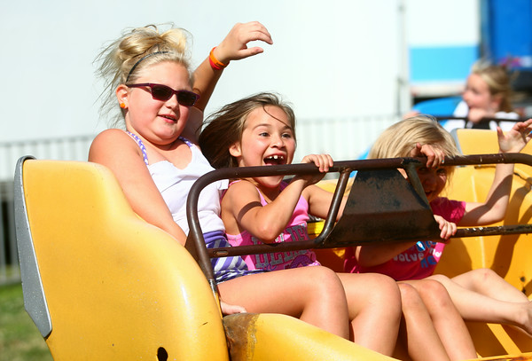 7-4-14<br /> Haynes Apperson Friday<br /> Sisters Abbie Davin, 9, Alyssa Swigart, 7, and  Alayna Swigart, 4, ride the Sizzler on Friday at the Haynes Apperson Festival.<br /> Kelly Lafferty | Kokomo Tribune