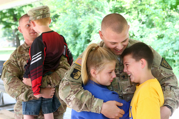 7-17-14<br /> Surprise soldier return<br /> David Lee hugs his two older kids, Maiah and Isiah, while his brother picks up and hugs his 6-year-old son Jacob. The Lee brothers surprised their kids Thursday afternoon at Highland Park after serving for nearly a year in Afghanistan.<br /> Kelly Lafferty | Kokomo Tribune