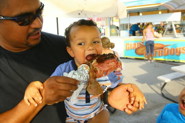 7-7-14 -- Cruz Bedoy with his 17 month-old son Max enjoying a turkey leg at the Howard County Fair.   ---<br /> Tim Bath | Kokomo Tribune