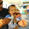 7-7-14 -- Cruz Bedoy with his 17 month-old son Max enjoying a turkey leg at the Howard County Fair.   ---<br /> Tim Bath | Kokomo Tribune