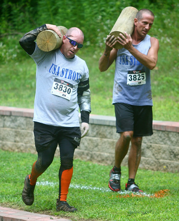 7-26-14<br /> Mud Battle<br /> Veteran Anthony Walton, who was wounded in Afghanistan, carries a log over his shoulder with Andy Smith of Indiana Pit during the Mud Battle at Oakbrook Valley. Walton is the first disable veteran to run and complete the entire course.<br /> Kelly Lafferty | Kokomo Tribune