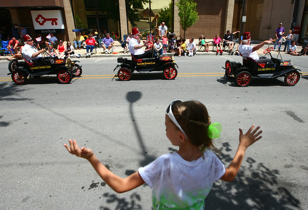 7-5-14<br /> Haynes Apperson Parade<br /> 8-year-old Maddy Cook waves to the Kokomo Shrine Club as they pass by during the Haynes Apperson parade.<br /> Kelly Lafferty | Kokomo Tribune