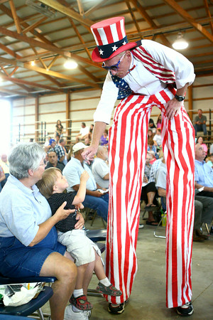7-10-14<br /> Fair--Thursday<br /> Kid Davie, dressed up as Uncle Sam, bends down to give 3-year-old Zavier Carter a tootsie roll before the start of the Livestock Auction at the Howard County 4H Fair.<br /> Kelly Lafferty | Kokomo Tribune