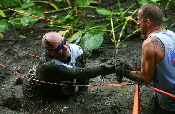 7-26-14<br /> Mud Battle<br /> Wounded Afghanistan veteran Anthony Walton gets a hand up by Indiana Pit's Andy Smith during the swamp portion of the Mud Battle at Oakbrook Valley. Walton is the first disabled veteran to run and complete the muddy obstacle course.<br /> Kelly Lafferty | Kokomo Tribune