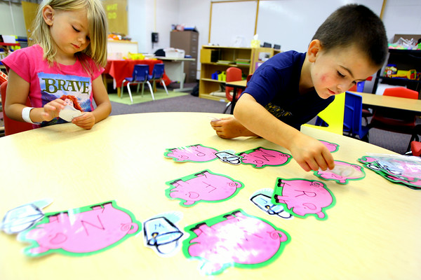 7-9-14 <br /> Lauren Nichols and Ricky Patton work with teacher Shane Metlock on letters using pictures during Early Head Start at Darrough Chapel.<br /> Tim Bath | Kokomo Tribune