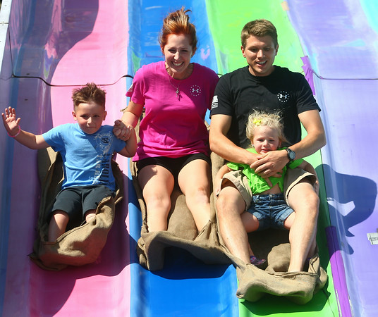 7-9-14<br /> Fair--Wednesday<br /> Samantha Coate and Jeff Vincent, along with their two kids Kayden Scheffer and Aerilyn Vincent, slide down the giant slide at the Howard County 4H Fair on Wednesday.<br /> Kelly Lafferty | Kokomo Tribune