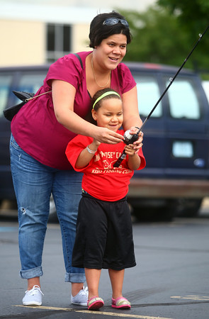 7-15-14<br /> Kids Fishing Clinic casting practice<br /> 6-year-old Katrell Gaillard gets a little help from her mom Leilani Peleti during casting practice for the Kids Fishing Clinic on Tuesday.<br /> Kelly Lafferty | Kokomo Tribune