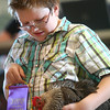 7-10-14<br /> Fair--Thursday<br /> Travis Pointer looks down at his hen as it gets auctioned off at the Howard County 4H Fair Livestock Auction.<br /> Kelly Lafferty | Kokomo Tribune
