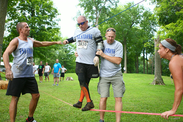 7-26-14<br /> Mud Battle<br /> Wounded Afghanistan veteran Anthony Walton gets a little assistance during a tightrope obstacle as part of Oakbrook Valley's Mud Battle. Walton is the first disabled veteran to run the Mud Battle course.<br /> Kelly Lafferty | Kokomo Tribune