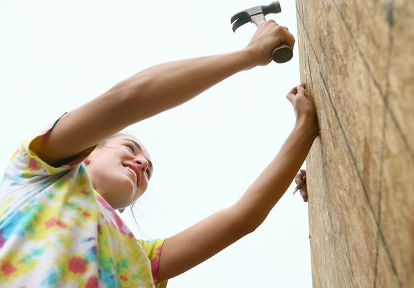 7-12-14<br /> Habitat for Humanity Apostles Build<br /> Megan Floyd of St. Patrick Catholic Church hammers a nail near the top of the Habitat for Humanity house on 1921 S. Bell Street during the Apostle Build on Saturday.<br /> Kelly Lafferty | Kokomo Tribune