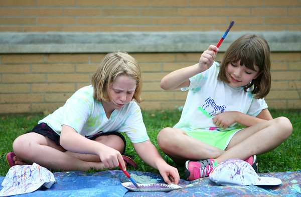 6-25-14<br /> Craft Fest<br /> 8-year-olds Johanna Hanneken (left) and Gretchen Powell splatter paint onto hats at one of the stations at the Craft Fest in Highland Park on Wednesday.<br /> Kelly Lafferty | Kokomo Tribune