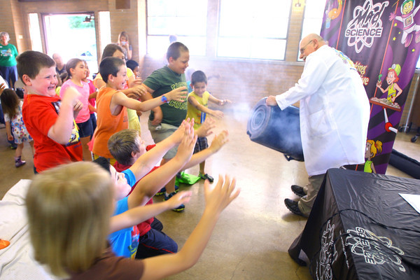 "6-3-14   --- ""Sizzlin'"" Sam Wendel does science demonstrations that wows and excited kids at Rogers Pavilion at Highland Park. Making smoke circles for the kids using air shoved through a small hole in the barrell.  --<br />   Tim Bath 