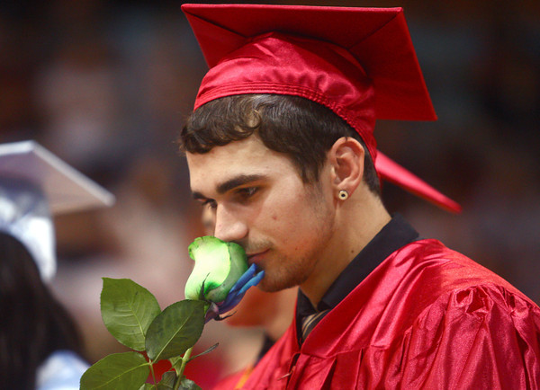 6-7-14<br /> Maconaquah Graduation<br /> Austin Rudicel smells the rainbow rose that each member of Maconaquah's Class of 2014 received after walking across the stage.<br /> Kelly Lafferty | Kokomo Tribune