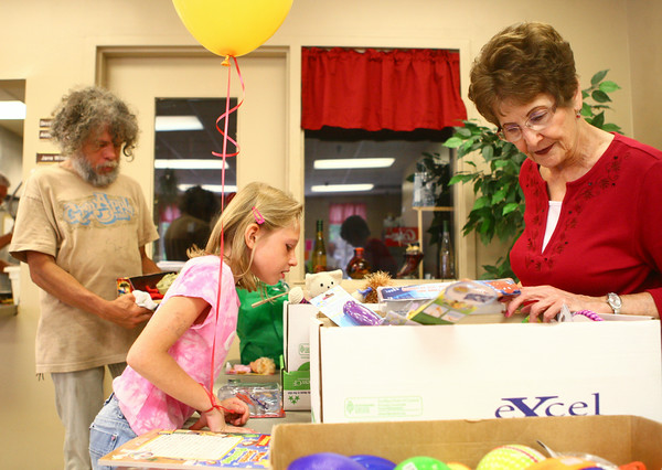 6-18-14<br /> Kokomo Rescue Mission birthday<br /> Pearl Gault (right) of Redeemer Lutheran Church looks through the boxes of toys at the Kokomo Rescue Mission to help Alivia Burkhard, 9, pick one out, as Mike Long (left) decides on what toys to get for his roommate's children.<br /> Kelly Lafferty | Kokomo Tribune