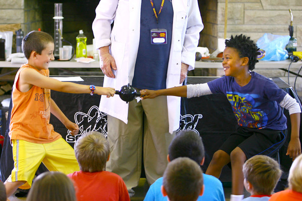 "6-3-14   --- ""Sizzlin'"" Sam Wendel does science demonstrations that wows and excited kids at Rogers Pavilion at Highland Park. Kellar Floyd and Camron pull on two hollow half spheres that were connected by air vacuumed out of the pieces thus holding them together. --<br />   Tim Bath 
