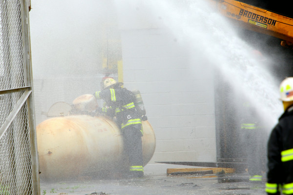 6-20-14   --- A propane leak at Moon Fabricating after workers tried to move the tank on Friday morning. Businesses surrounding the business at Morgan and Davis Roads were evacuated for about an hour till firefighters were able to contain it. KFD Aaron Ashburn checks the leak to make sure it has been shot off or depleated while water is sprayed on the tank to neutralize the gas. --<br />   Tim Bath | Kokomo Tribune