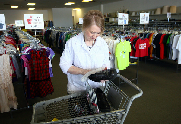 6-27-14<br /> Salvation Army Thrift Store<br /> Sorter and cashier Jennie Maki cleans off shoes before they are displayed at the new location of the Salvation Army Thrift Store.<br /> Kelly Lafferty | Kokomo Tribune