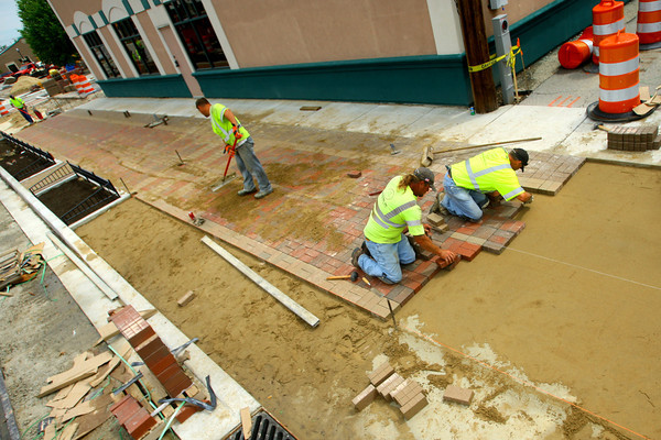 6-11-14   --- E & B Paving workers Jason Henderson, Dave Steelman and Darryl Wood work on putting in pavers along along the trail on Buckeye Street downtown between Taylor and Mulberry Streets.    --<br />   Tim Bath | Kokomo Tribune