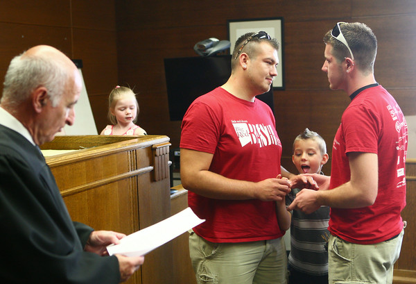 6-27-14 <br /> Same sex weddings<br /> Joshua Day and Brandon Patrick exchange rings over the watchful eye of Day's son, Cayden Day, as Joshua's neice Isabella Prater plays in the courtroom behind them. Day and Patrick, who were the first same-sex couple to get a marriage license in Howard County were married at the Howard County Courthouse by Judge Hopkins on Friday afternoon.<br /> Kelly Lafferty | Kokomo Tribune