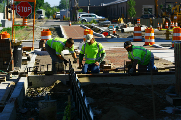 6-5-14   --- E & B Paving workers Jason Henderson, Dave Steelman and Darryl Wood work on putting in pavers along along the trail on Buckeye Street downtown between Taylor and Mulberry Streets.    --<br />   Tim Bath | Kokomo Tribune