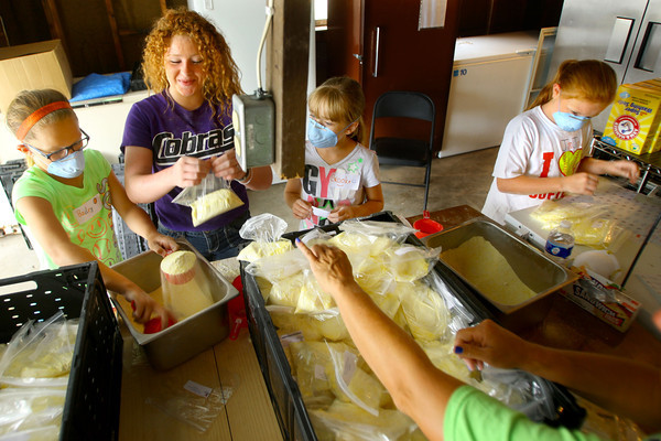 6-10-14   --- Kids volunteer at Urban Outreach in a new program called Kids4Kids.  Bailey Henry, 9, Kaylin Trine, 15, Brooke Hughes, 10, and Jojo Trine, 10, scooping laundry detergent into ziploc bags that will be given out in the food pantry.  --<br />   Tim Bath | Kokomo Tribune