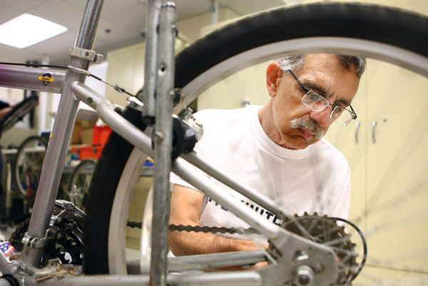 6-20-14<br /> Mike McDermott repairs a bicycle in the basement of Delphi on Friday morning.<br /> Kelly Lafferty | Kokomo Tribune