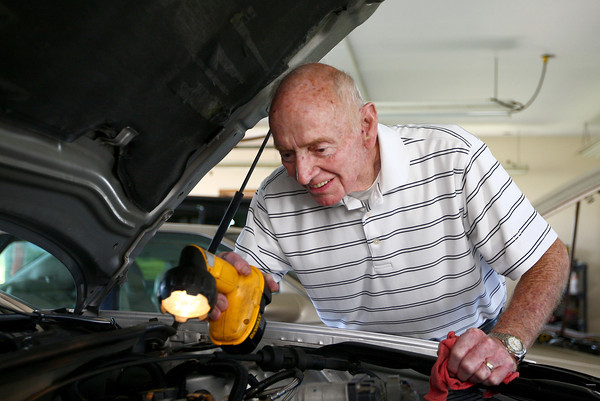 6-3-14<br /> Dick Smith mechanic<br /> Dick Smith, who's been a mechanic for 56 years, uses a flashlight to look under the hood of one of the cars in his Kokomo garage.<br /> Kelly Lafferty | Kokomo Tribune