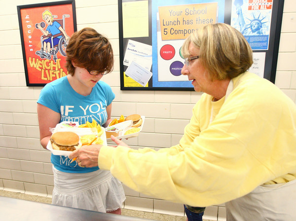 6-24-14<br /> Taylor Primary Lunch<br /> Cathy Smith helps Michele Cowart carry two trays as she gets lunch at Taylor Primary.<br /> Kelly Lafferty | Kokomo Tribune