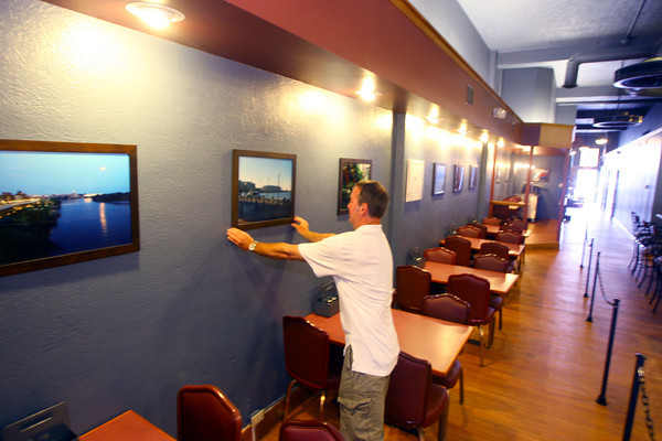 6-2-14   --- New downtown bar called the district opening June 5. Owner is Todd Rudicel straightens photos he shot that line the wall. --<br />   Tim Bath | Kokomo Tribune