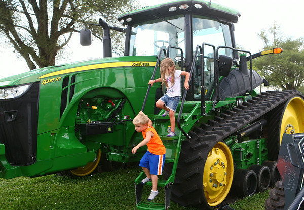 6-25-14<br /> Miami County Fair<br /> 5-year-old twins Kobe and Kyree Delk play on one of the tractors set up at the Miami County Fair.<br /> Kelly Lafferty | Kokomo Tribune