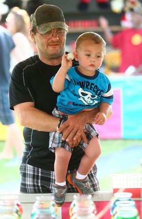 6-25-14<br /> Miami County Fair<br /> David Shuck holds his 15-month-old grandson Mason Walsh as he tries to throw the ball into one of the jars to get a fish.<br /> Kelly Lafferty | Kokomo Tribune