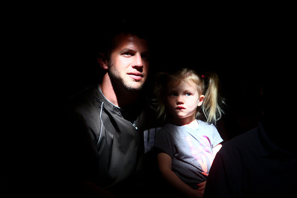 5-9-14<br /> Kelly Miller Circus<br /> Caden Cline and his 2-year-old daughter Sophia Cline are illuminated in the audience as they watch the Kelly Miller Circus under the big top on Friday. <br /> Kelly Lafferty | Kokomo Tribune