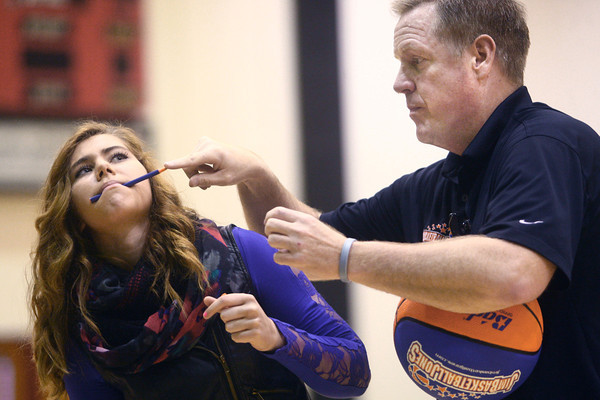 """3-19-14<br /> Jim """"Basketball"""" Jones anti-bullying<br /> Jim """"Basketball"""" Jones shows how he is going to spin and balance a basketball on a pen in Kendra Perkins' mouth at Western High School.<br /> KT photo   Kelly Lafferty"""