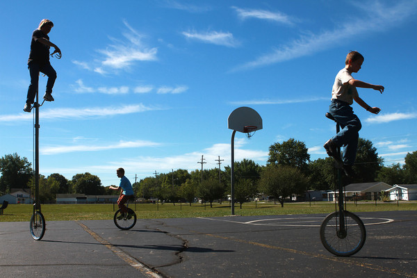 Tom Miller Unicyclist<br /> Tom Miller, Cameron Lloyd, and Kyle Fortier ride unicycles of different heighths on the basketball court of Bon Air Elementary on a summer day.<br /> KT photo | Kelly Lafferty