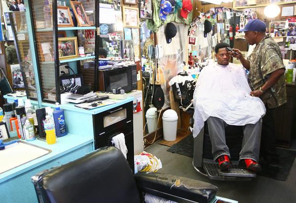 3-20-14<br /> Earl Davis Barbershop<br /> Earl Davis of Davis Barbershop on N. Apperson gives Michael Burris a haircut.<br /> KT photo | Kelly Lafferty