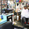 3-20-14<br /> Earl Davis Barbershop<br /> Earl Davis of Davis Barbershop on N. Apperson gives Michael Burris a haircut.<br /> KT photo | Kelly Lafferty