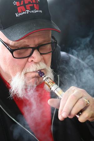 3-28-14<br /> Kokomo Pure Vapors<br /> Jeff Lamberson uses an e-cigarette in his shop, Kokomo Pure Vapors.<br /> KT photo | Kelly Lafferty