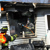 3-26-14   --- Kokomo firefighters battle a house fire at 517 Edgewater Drive in Kokomo on Wednesday afternoon. The fire started in the rear with noone in the house. A hose is handed out the window to put out a few hot spots on the outside of the house. -- <br />   KT photo   Tim Bath