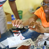 2-19-14   --- The Haitian Environmental Support Program(H.E.S.P.) founded by Doug Vaughn and the Lions Club traveled to Pilate, Haiti to fit about 1500 Haitians with glasses. Anita Upchurch helps a Haitian man with an eye glass fitting.  -- <br />   KT photo | Tim Bath