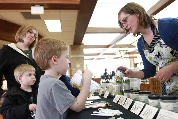 3-11-14<br /> Converstations at the library<br /> Cara Retz (right) helps make a snack for 5-year-old Gabe Damron, as Brittany Damron and 4-year-old Jude Damron watch.<br /> KT photo | Kelly Lafferty