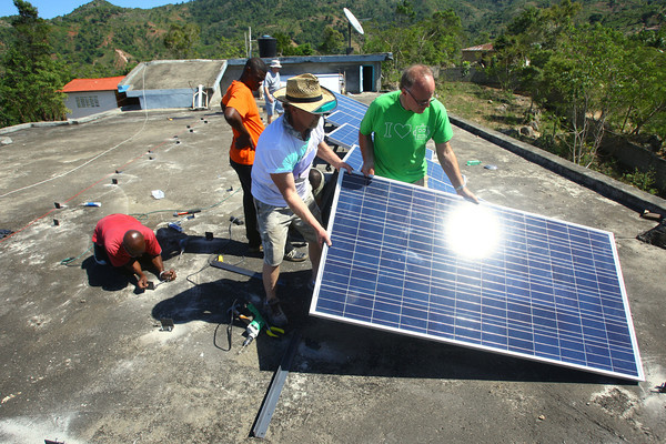2-18-14   --- Solar Electric system installed in Bas Limbe, Haiti at Our Lady of Mt Carmel Catholic Church. Gary Maggard and Mark Koors install one of the sixteen 300 watt solar panels on the roof of the school. -- <br />   KT photo | Tim Bath