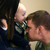 11-18-13<br /> Homecoming of the 434th Air Refueling Wing to Grissom<br /> Tabatha Janssen holds baby Zehdyn Janssen as Zehdyn's dad, David Bryant, kisses him on the stomach after Bryant  returned to Grissom from a deployment with the 434th Air Refueling Wing in southeast Asia.<br /> KT photo | Kelly Lafferty