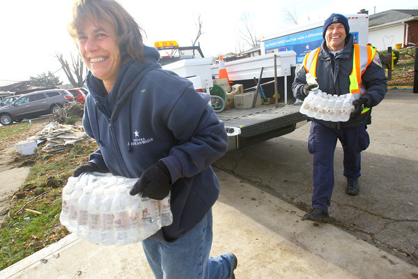 Pam Fivecoate from Indiana American water and KPD officer Jim Gunlite bring water to a food site in the Cedarcrest area that was ravaged by the tornado.<br />   KT photo   Tim Bath