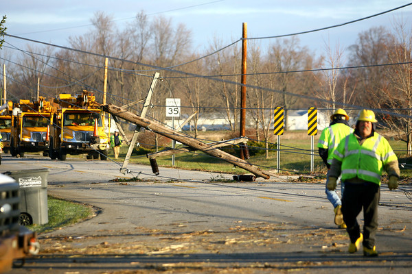 The tornado took down the high voltage wires and poles on Guyer Road on Sunday. Pike Electric workers out of Cincinnati remove and replace the lines on Tuesday.<br />   KT photo | Tim Bath