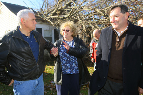 11-18-13  --  Gov Mike Pence comforts Patsy Addison as the governor tours the damaged areas. Behind her you can see the tree that has crashed through the roof of her and her husbands house. US Sen. Joe Donnelly is also with the governor.<br />   KT photo | Tim Bath