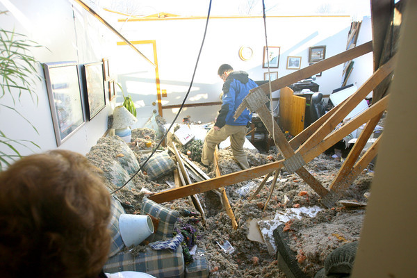 Derek Stone from Fire & Flood Recovery sifts through the remains of Jean Sanner's family room after the tornado came through. Her house on Buick Lane in Cedar Crest was assessed as a total loss.<br />   KT photo   Tim Bath